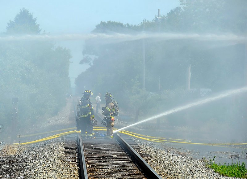 Firefighters shoot a stream of water from the railroad tracks to the Galaxy nightclub. A recent inspection of the building found a few minor wiring problems, but nothing unusual.