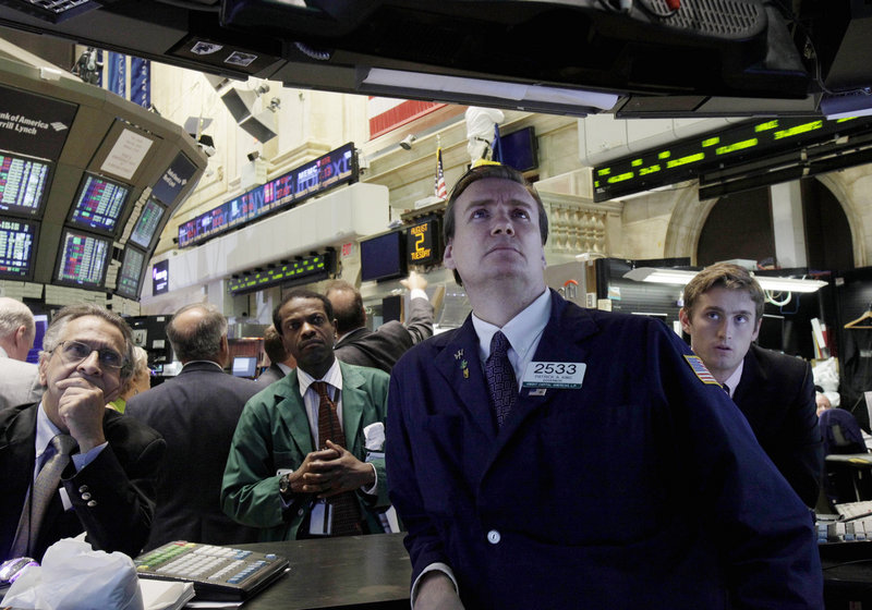Patrick King, second from right, and others watch President Barack Obama's remarks on a television monitor from the floor of the New York Stock Exchange on Tuesday.