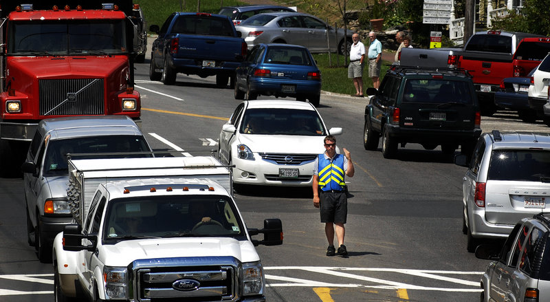 Wiscasset police Officer Alex Greenlaw directs traffic through downtown Wiscasset on Tuesday. Many residents and merchants welcomed the Maine Department of Transportation's decision to call off plans for a bypass around the town.