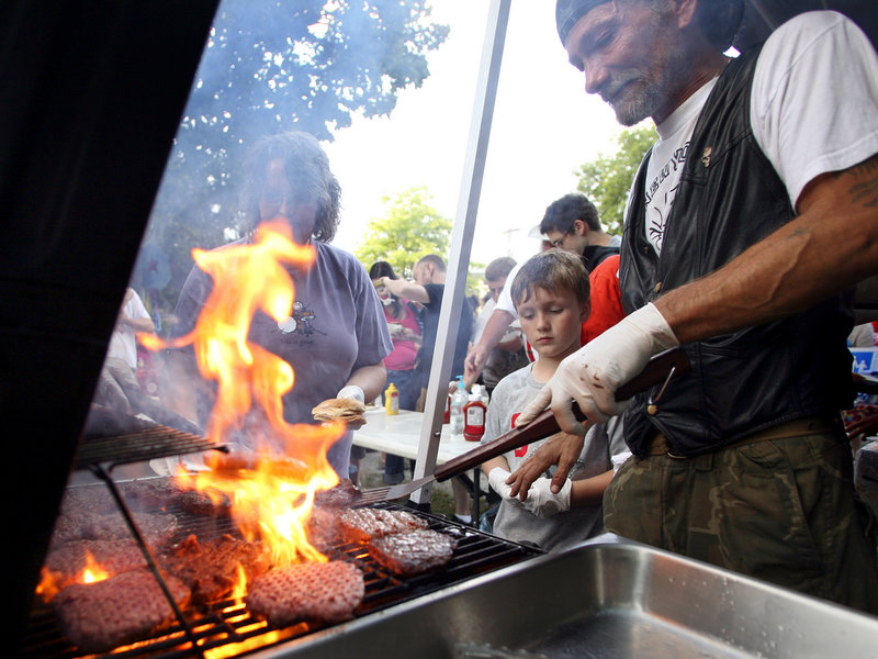 Bill Sidelinger, an East Bayside resident, grills burgers in Peppermint Park Tuesday as part of National Night Out. This is a good way to show the children that the neighborhood they live in is safe, said resident Ann Marie Tucker.