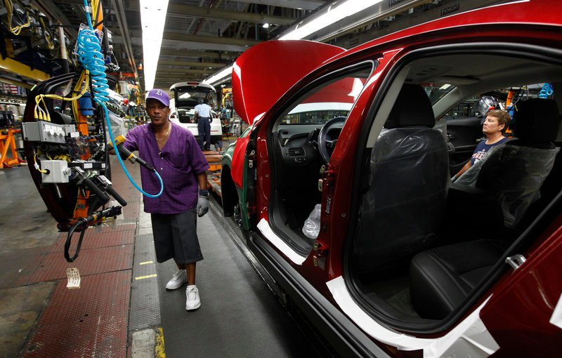 Assembly line worker Edward Houie moves a door into position for a 2012 Chevrolet Volt last month at GM's assembly plant in Hamtramck, Mich. GM's sales rose 7 percent in the second quarter to 2.3 million cars and trucks.
