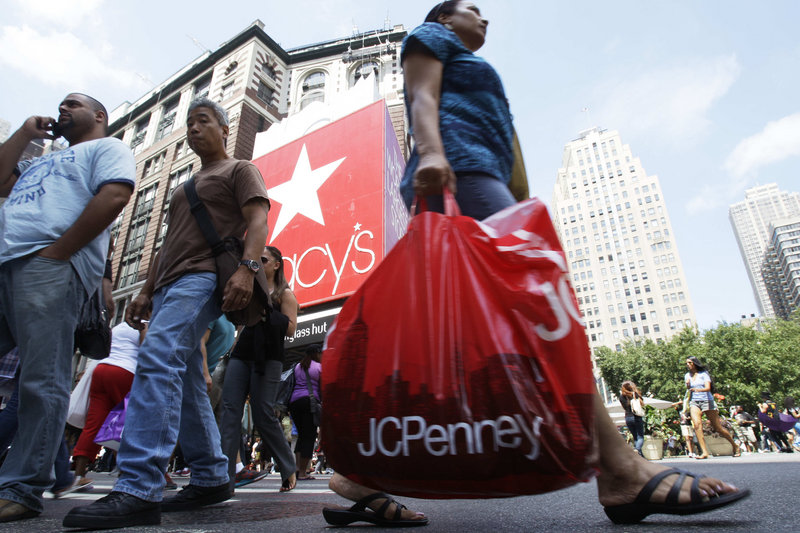 Shoppers pass Macy's department store Thursday in New York. Discounts and sweltering heat in July drove back-to-school bargain hunters to air-conditioned malls.