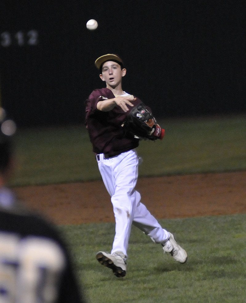 Ryder Kenney of Fayette-Staples keeps his concentration while unleashing a throw to first base to get the runner.