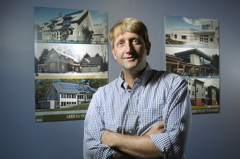Gunnar Hubbard, an architect who is the founder and CEO of Fore Solutions, a green building consulting firm, stands in front of photographs of a few of the projects his company has worked on in Maine.
