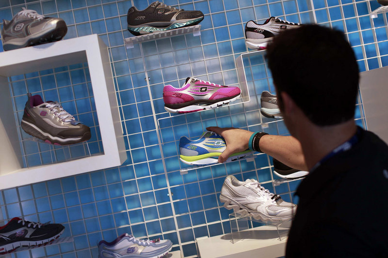 An employee adjusts a Skechers running shoe in a Manhattan Beach, Calif., store. The company is trying a lighter line.