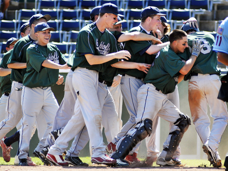 Matt Pagano is mobbed by his teammates Friday after scoring the winning run for Cranston, R.I., in the 10th inning in a game that eliminated host team Fayette-Staples from the American Legion Northeast Regional at The Ballpark in Old Orchard Beach. Mike Hayden s sacrifice fly won it.