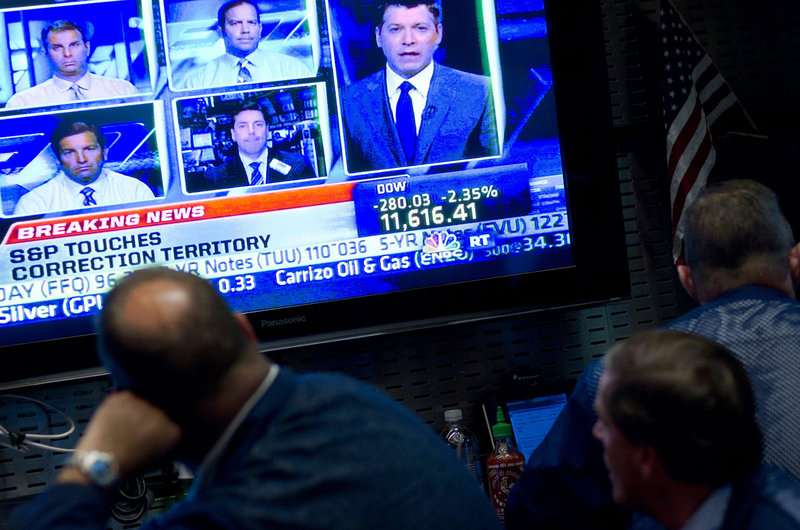 A monitor displays the plummeting Dow Jones Industrial Average and a host of news analysts and commentators weighing in as traders watch on the floor of the New York Stock Exchange on Thursday.