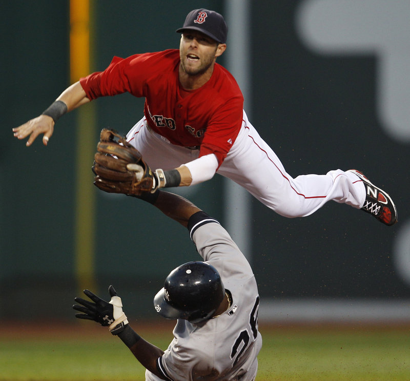 Dustin Pedroia of the Boston Red Sox leaps over Eduardo Nunez of the New York Yankees and fires to first in the third inning Friday night. Nunez was out on a force but Derek Jeter beat the throw to first.