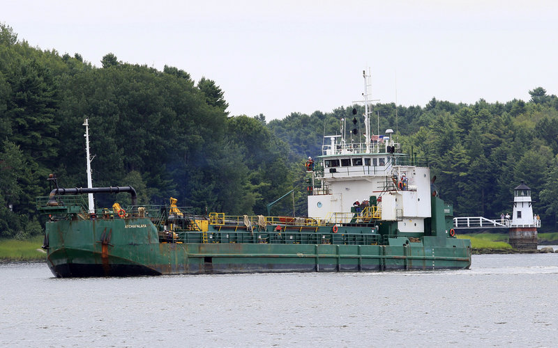 Spectators watch a dredger deepen a channel in the Kennebec River, upstream from the Doubling Point Light in Arrowsic on Friday. The Army Corps of Engineers began the work after the BEP and a federal judge rejected petitions to stop it.