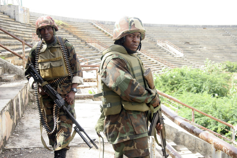 Ugandan peacekeepers and Somali government troops stand guard inside the Mogadishu, Somalia, sports stadium. The stadium was a base for al-Shabab Islamist militants until early Saturday, when al-Shabab withdrew from their bases throughout Mogadishu.