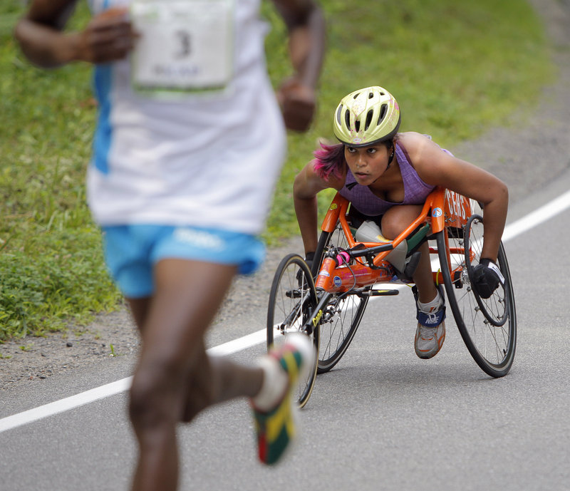 Christina Kouros, a Cape Elizabeth resident, pushes up a hill on Shore Road while being passed by runner Micah Kogo, the overall winner.