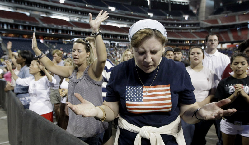 Lucy West of Killeen, Texas, prays at The Response, a call to prayer for a nation in crisis Saturday in Houston, Texas. Gov. Rick Perry attended the daylong prayer rally despite criticism that the event inappropriately mixed religion and politics.