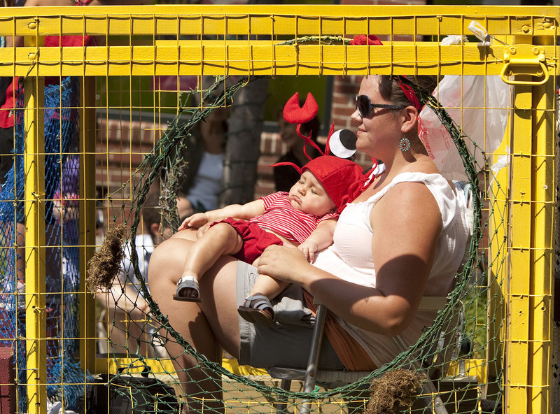 On a lobster-trap float during Saturday's parade, Rachel Winchenbach holds her 7-month-old daughter, Leandra, who remains blissfully unaware of the goings-on.