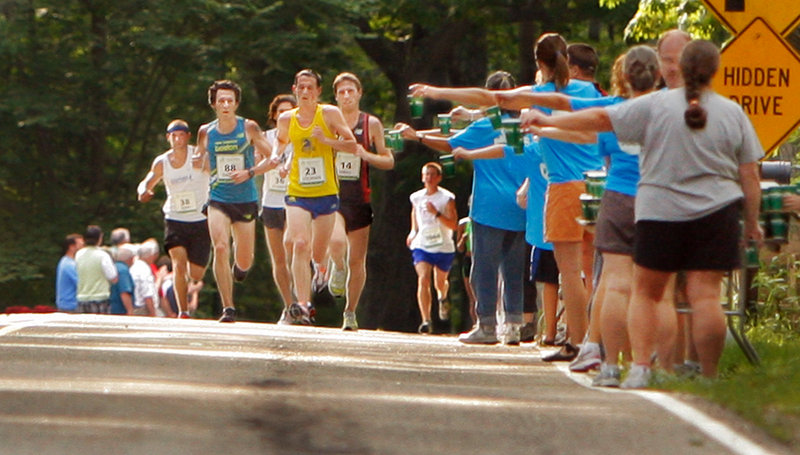 Volunteers hold out water to runners along Shore Road in Cape Elizabeth during the TD Bank Beach to Beacon 10K Saturday. To some runners, finishing fast is important. To others, just finishing makes them proud.