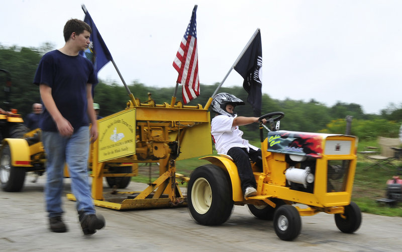 Calvin Curro, 9, of Biddeford holds on as he rips down the dirt track during the tractor pull in Saco on Sunday that benefited the Make-A-Wish Foundation.