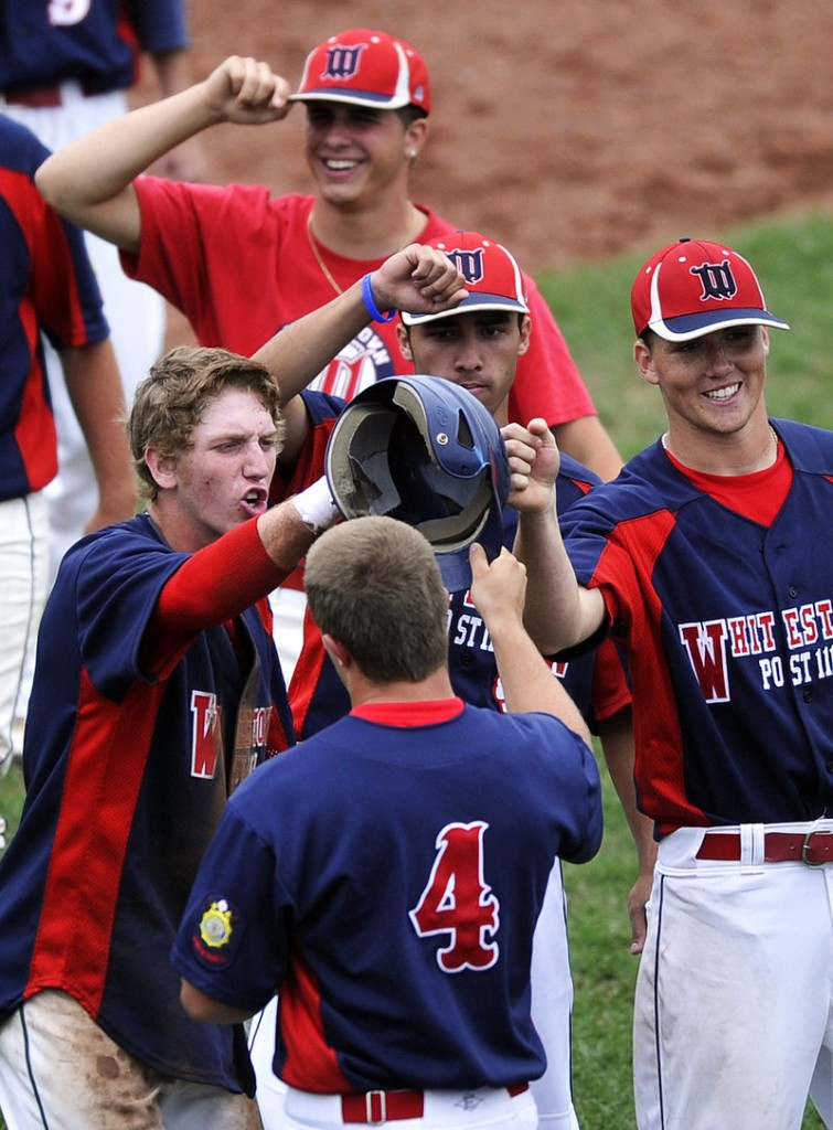 Brendan Heitz, front, is congratulated by his teammates after scoring a run Sunday to help Whitestown, N.Y., break open its elimination game with Norwalk, Conn. Whitestown won, 9-5.