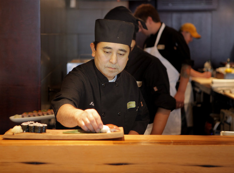 Chef Masa Miyake prepares lunch at his restaurant on Fore Street in Portland. This summer some of the food served at Miyake's two restaurants has been produced at the farm behind his home in Freeport.