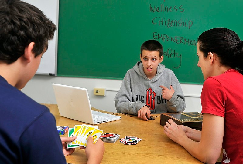 Kat Seevers, 15, center, talks with fellow student Garrett Ferland, 16, left, during a game of Uno. At right is Tamber Woodman, an educational technician.
