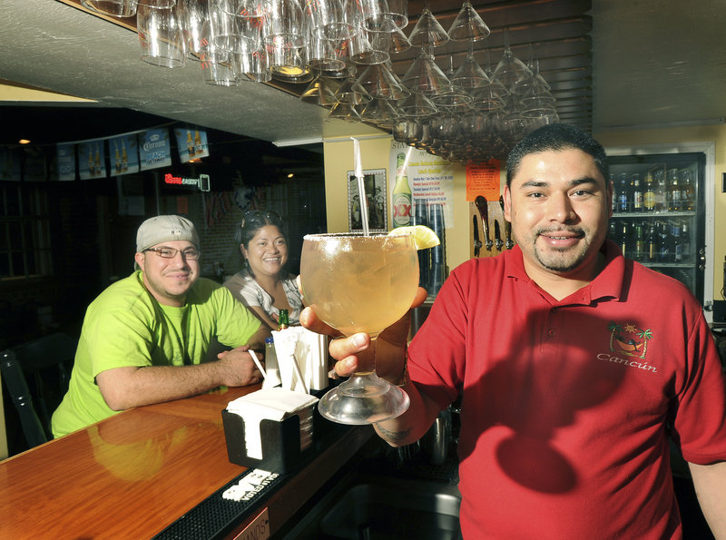 Bartender Gama Chavez serves a margarita to Adam Smith and Thea Hernandez at Cancun in Biddeford. Mix-and-match food platters complement Cancun's big drinks.