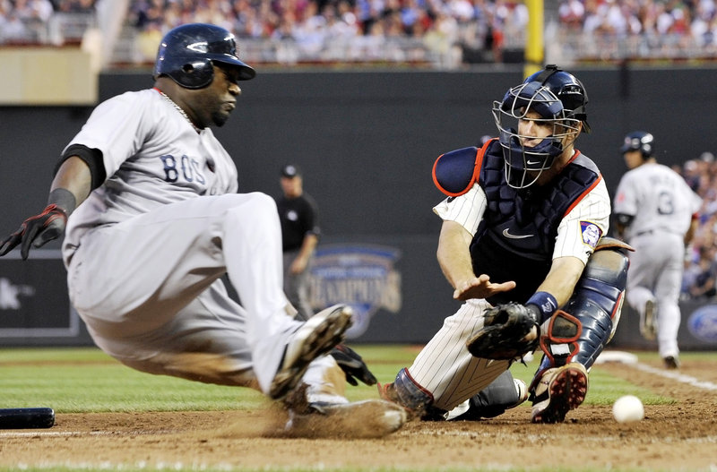 David Ortiz slides safely into home as Twins catcher Joe Mauer fails to handle the throw in the eighth inning Monday night. Ortiz went 4 for 5 and drove in the go-ahead run in the ninth inning, giving the Red Sox a 8-6 victory.