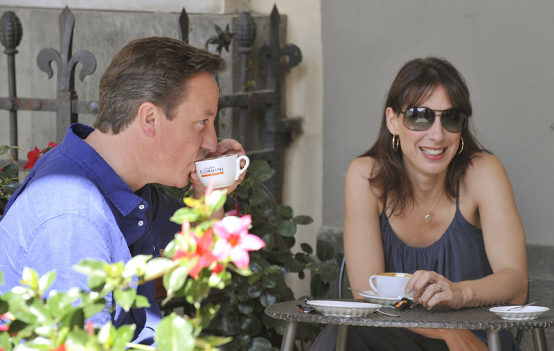 Britain's Prime Minister David Cameron and his wife Samantha sit at a cafe July 31 on the second day of their holiday in Tuscany. Cameron recalled Parliament on Tuesday, interrupting the summer recess.