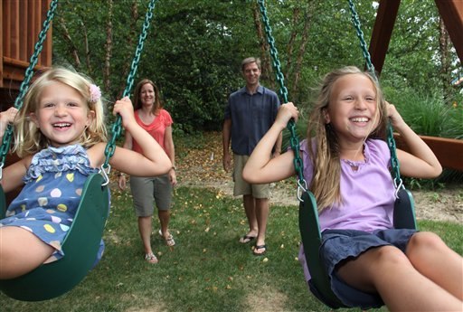 Anna, 8, right, and Sophia, 5, left, get pushed on their swing set by their parents, Maria and John Seyerle, in the backyard of their new home in Wyoming, Ohio. A swing set was on the girls' wish list for a new house.