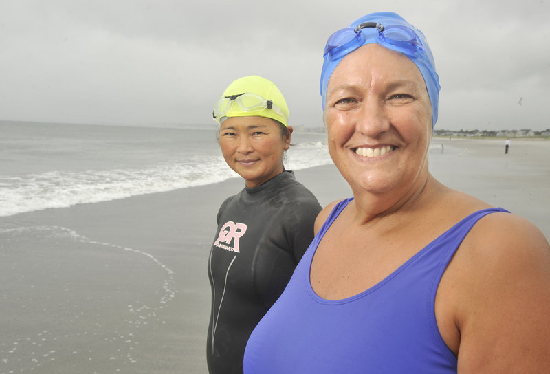 Pat Gallant-Charette, right, of Westbrook was inspired to become a distance swimmer after the death of her brother. Yoko Aoshima of Falmouth, who joins Gallant-Charette during her training sessions at Pine Point Beach in Scarborough, has been similarly inspired by her swimming partner.
