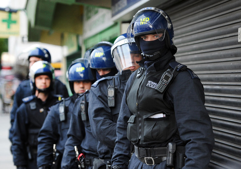 Metropolitan Police officers prepare to carry out a raid Thursday at the Churchill Gardens estate in the Pimlico section of London. Police were hoping to recover property stolen during the recent rioting in the capital.