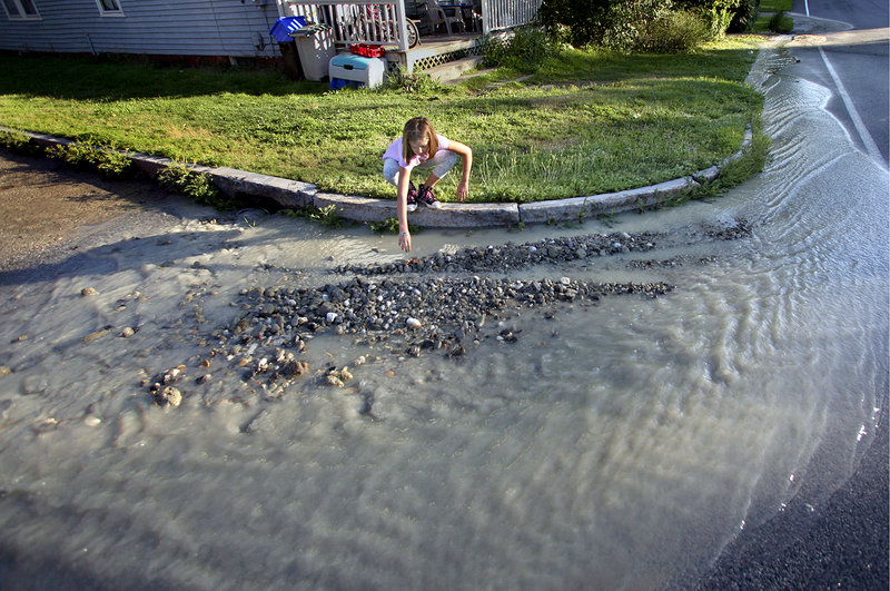 Caitlin Dirocco, 9, of Portland picks through rocks and clay in front of her house that had traveled from a water main break a couple blocks away, at the intersection of Washington Avenue and West Kidder Street, on Thursday.
