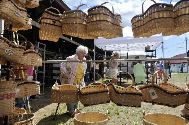 Marion Bergman of Haverhill, Mass., looks over handmade baskets by Julie Eugley of Greenfield Township during the 42nd annual Cumberland Arts & Crafts Show on Friday. The show continues today and Sunday.