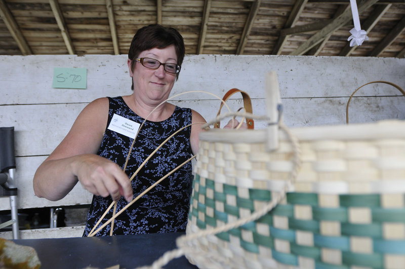 Dawn Seaward of Mountain View Baskets in Acton weaves a basket during the Cumberland Arts & Crafts Show on Friday.