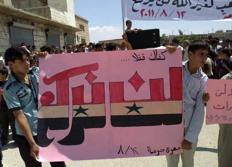 """Protesters hold an Arabic banner reading """"Enough killing, will not bow"""" during a demonstration Friday against the Syrian regime in Maarat Harma village in northern Syria. The image was taken with a mobile phone and provided by the Shaam News Network. Syria has banned most foreign journalists."""