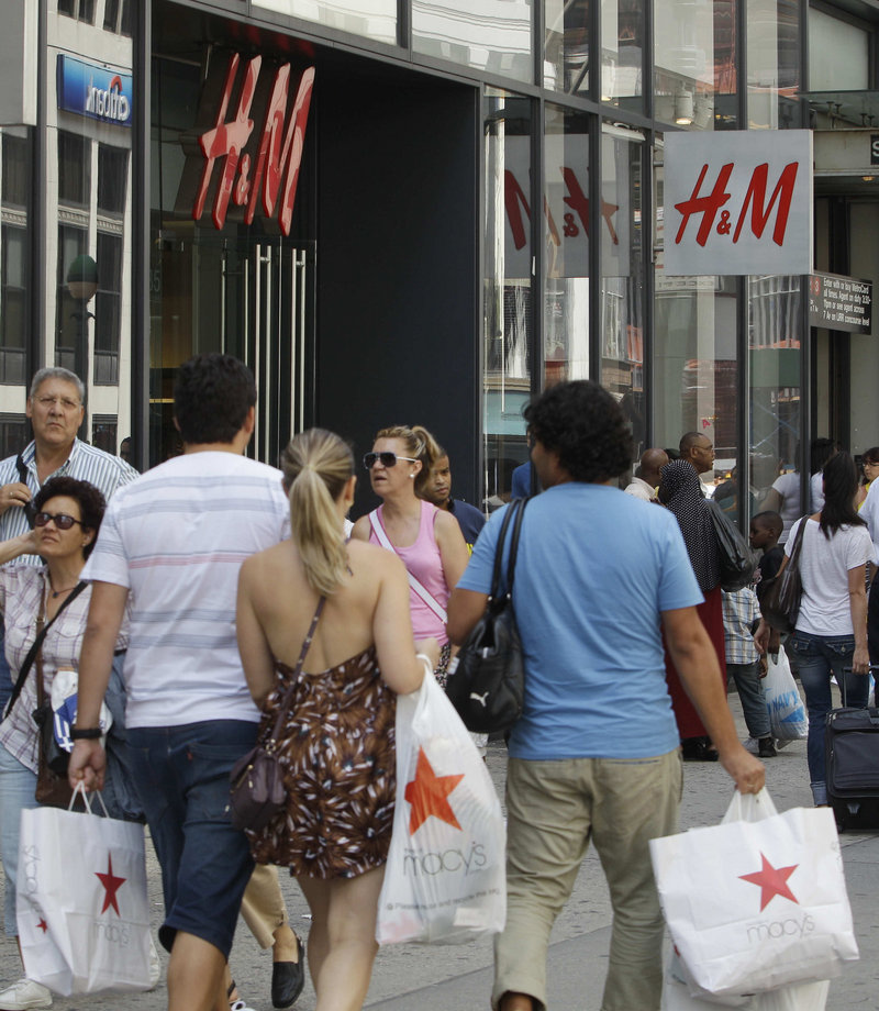 Shoppers carry purchases past H&M in New York. Consumers, who drive most economic growth, spent more on cars and other goods in July – and more in May and June than previously thought.