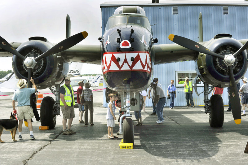 Veterans and children are among visitors examining a World War II-era B25 bomber at the Wiscasset Municipal Airport on Saturday. The six planes are maintained and flown by The Texas Flying Legends, a nonprofit group that is considering creating a summer base in Maine for its extensive collection.