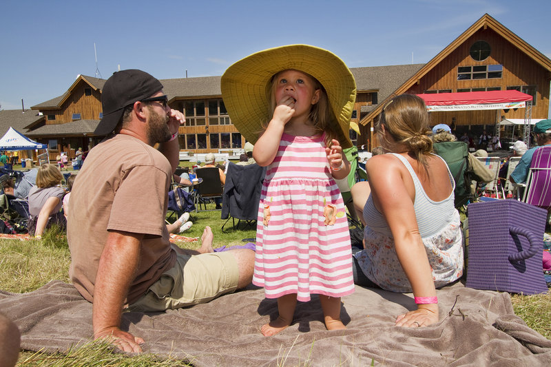 Fern Carter-Hill, 2 1/2, of Oxford checks out the festival scene as her parents, Jesse Hill and Sarah Carter, listen to a performance.