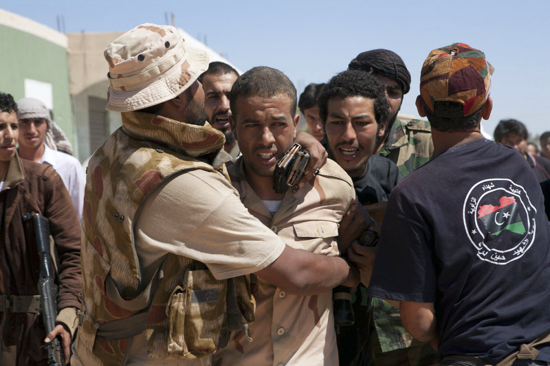 Libyan rebels protect a captured enemy sniper from other rebels near Zawiya, Libya, on Saturday. The prisoner, whose name had not been released yet, was driven away.