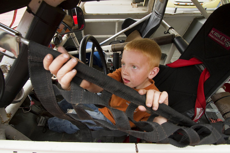 Adrien Williams, 6, of South Thomaston closes the screen on his grandfather's car during the Maine Vintage Race Car Association show on Sunday.
