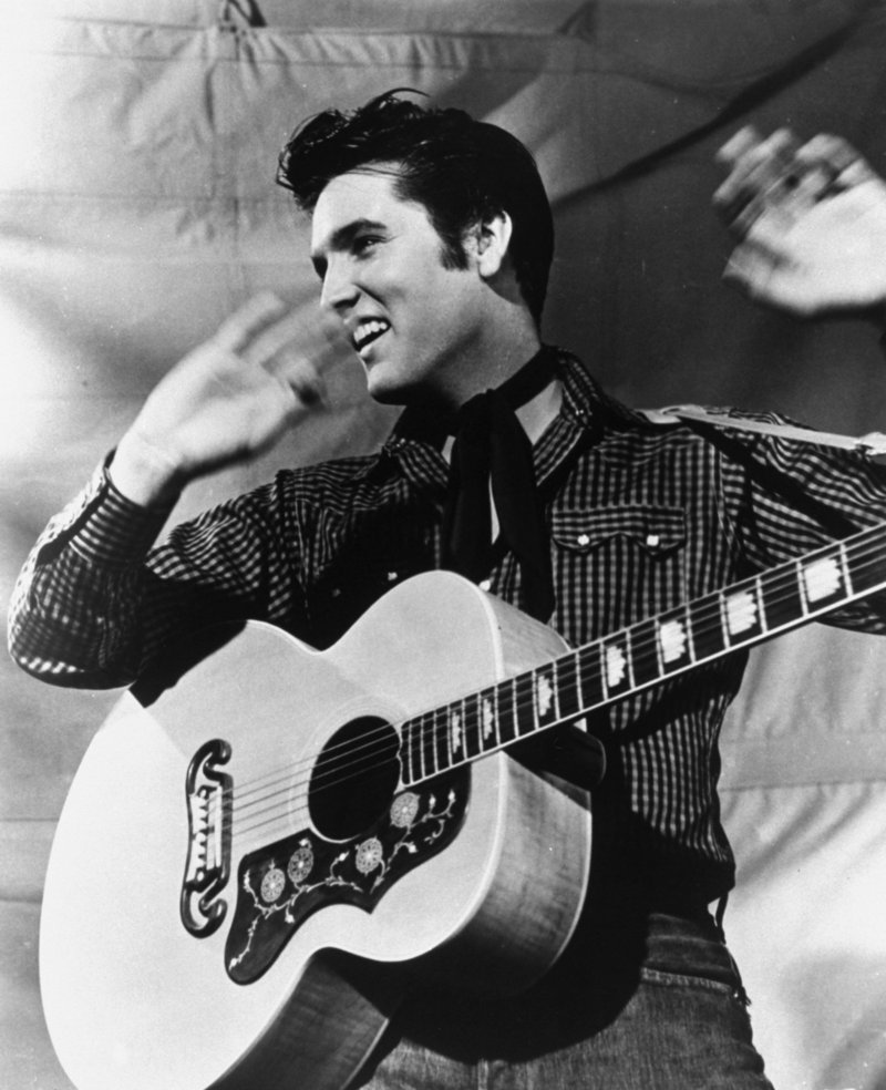 Elvis Presley is shown with his Gibson guitar in 1957. In 1956, 55 years ago, the King released his first two albums, launching his international career.