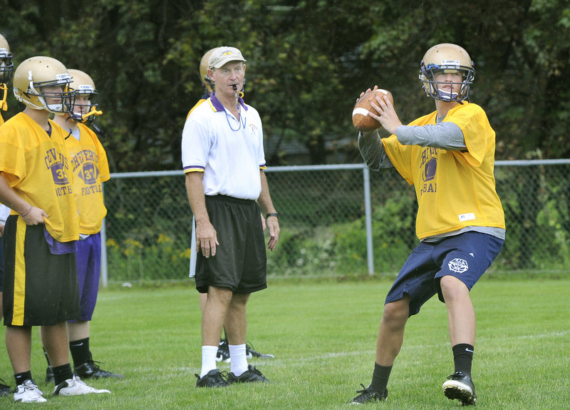 Cheverus Coach John Wolfgram watches senior quarterback Cam Olsen during the Stags first day of training at their Ocean Avenue practice field.