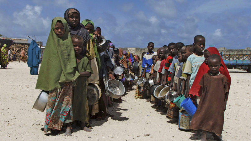 Holding their pots, children from southern Somalia line up to receive cooked food in Mogadishu on Monday. Much of the food aid being sent to Somalia doesn't reach the starving.