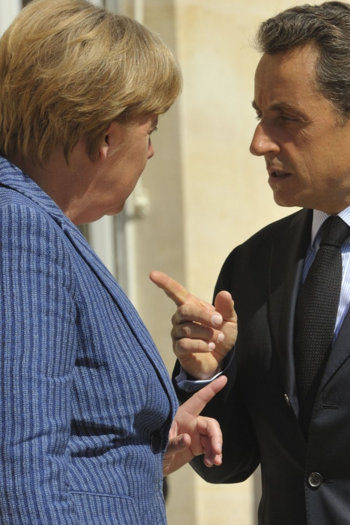 French President Nicolas Sarkozy, right, and German Chancellor Angela Merkel gesture before an emergency meeting Tuesday in Paris.