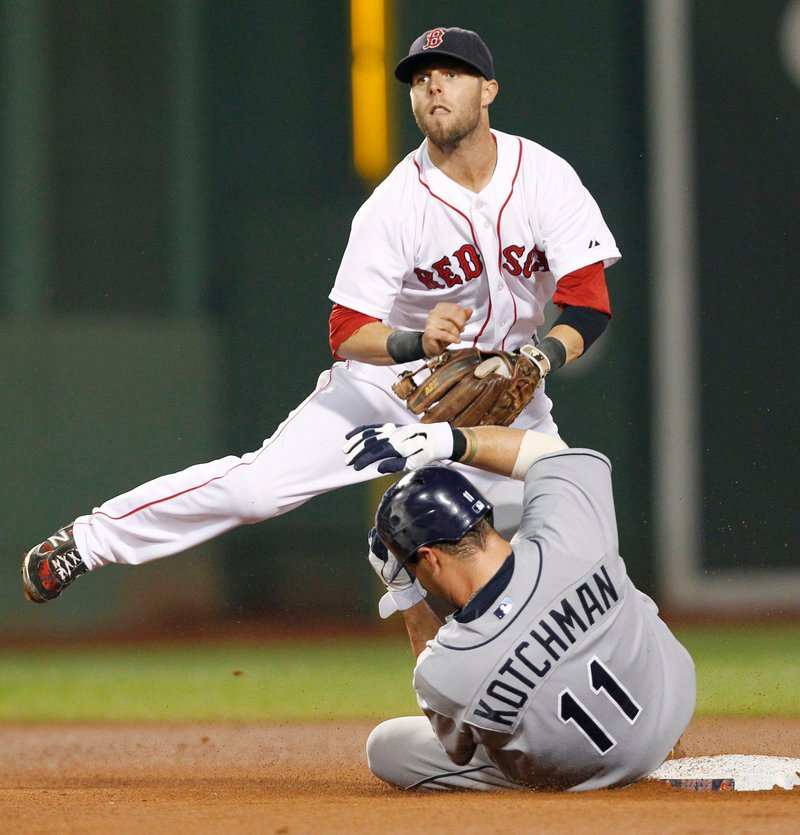 Dustin Pedroia of the Boston Red Sox keeps his eye on the throw to first base after forcing Casey Kotchman of the Tampa Bay Rays at second. Pedroia's throw was on time and completed the first triple play for the Red Sox since John Valentin registered an unassisted triple play against the Seattle Mariners in 1994.