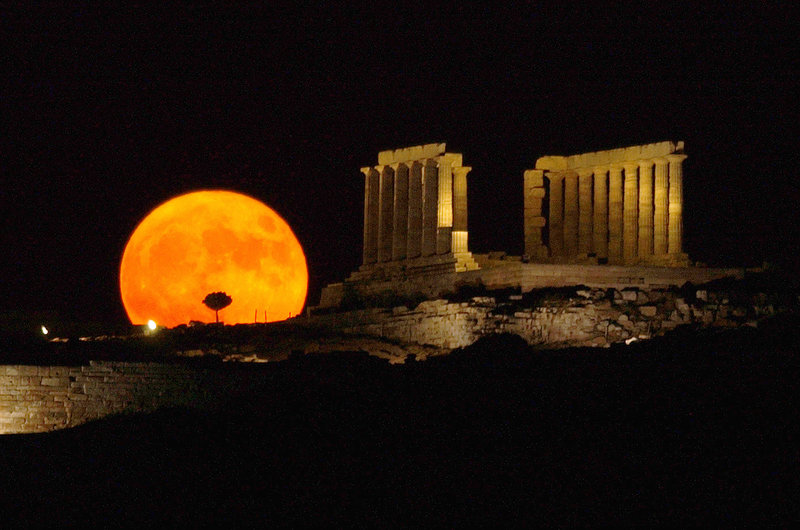 The full moon, possibly 200 million years younger than once thought, rises behind the ancient temple of Poseidon in Sounio, Greece, about 45 miles from Athens.