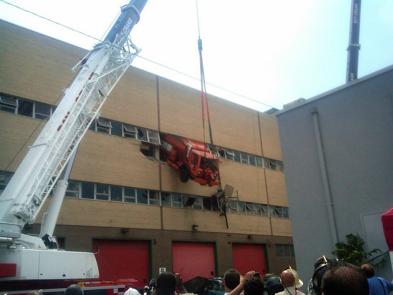 A salt-spreading truck dangles from a building in the New York borough of Queens, suspended from a crane, after it drove through the wall of a repair shop. Firefighters used a cherry-picker to rescue driver Robert Legall, a mechanic who was hospitalized in stable condition.