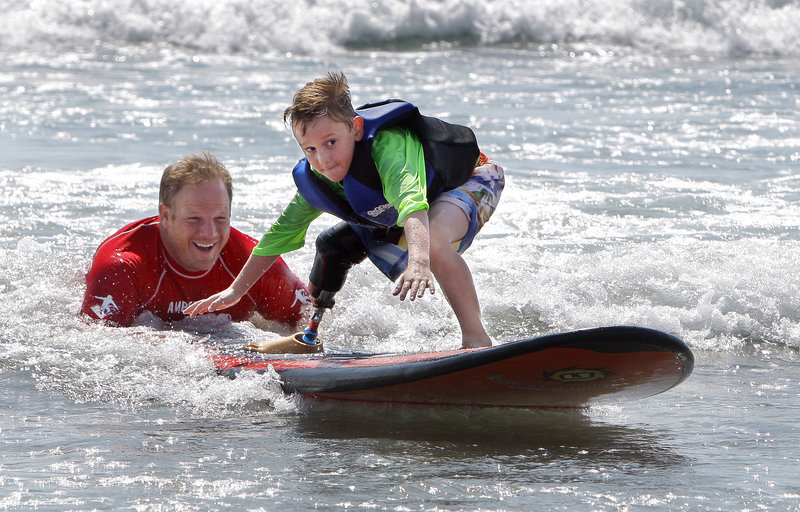 Shaun McLaughlin, a Natick, Mass., 6-year-old who was born without a right foot, learns how to surf with help from Dana Cummings at Long Sands Beach in York on Thursday. Cummings, a Maine native, leads AmpSurf, an organization that teaches people with disabilities how to surf.