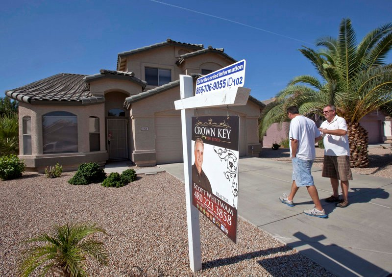 Real estate broker Kurt Sabel, right, talks with prospective buyer Ned Pierce outside a home Wednesday in Gilbert, Ariz. U.S. home sales fell 3.5 percent in July.