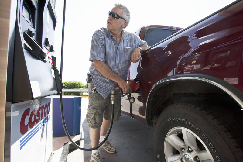 Gary Hartwig of Gretna, Neb., fuels his car at a Costco station in Omaha. Food and gas took a deeper bite out of paychecks last month.