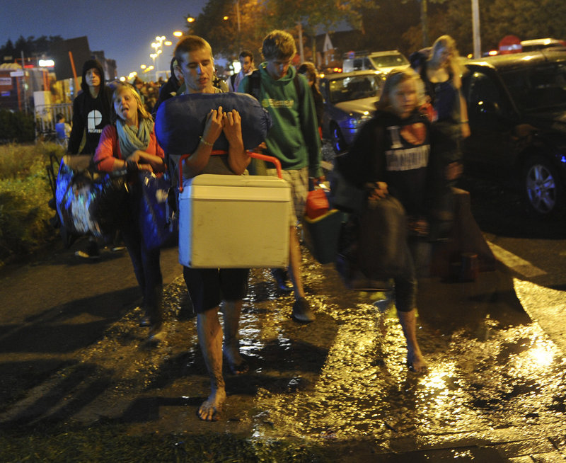 Concertgoers file away from an outdoor festival in Hasselt, Belgium, Thursday night after a sudden storm knocked down structures, killing three people and injuring more than 70.