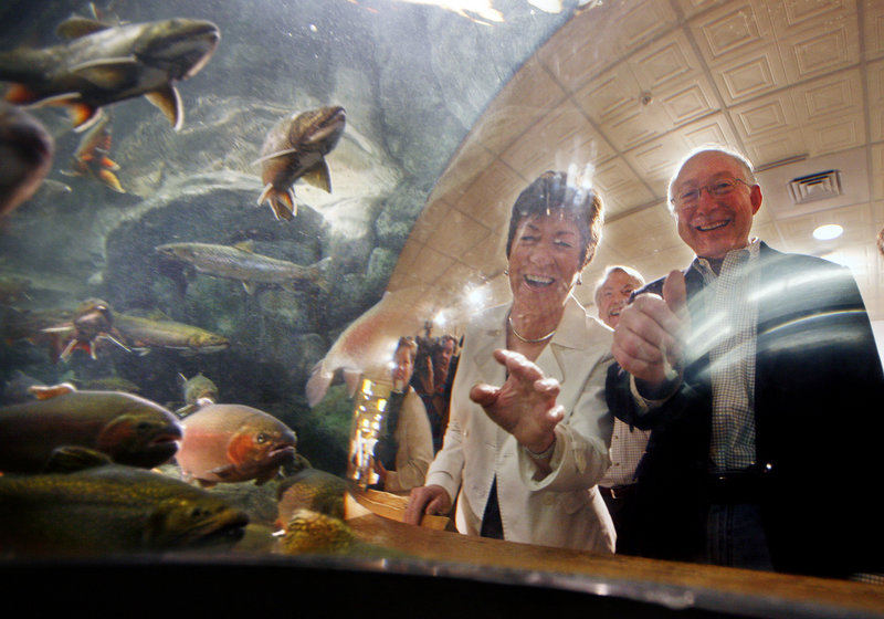 Sen. Susan Collins, R-Maine, and Interior Secretary Ken Salazar peek into an aquarium containing trout and salmon during a visit Thursday to the L.L. Bean retail store in Freeport.