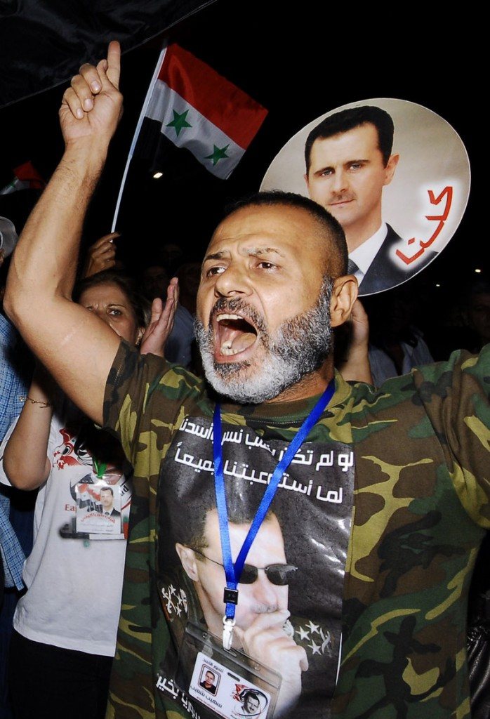 A supporter of Syrian President Bashar Assad, whose portrait is on his T-shirt, demonstrates in Damascus on Friday. Assad, who inherited power from his father in 2000, is facing the most serious international isolation of his rule.